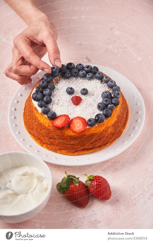 Faceless lady serving cake with berries baked dessert cooking woman decorating blueberry strawberry sour cream female chef homemade household penguin plate dish