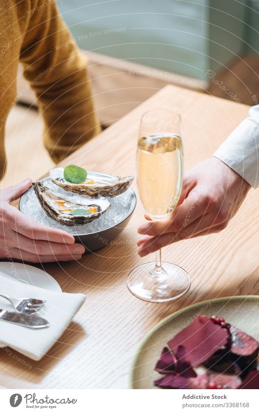 Crop person enjoying oysters and champagne eat drink restaurant lemon herb ice table clam seafood exquisite delicious tasty yummy palatable delectable savory