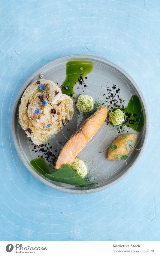High cuisine dish of seafood salmon restaurant pike caviar cabbage sauce high cuisine haute cuisine plate served decoration fish dinner gourmet fresh fillet