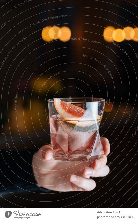 Anonymous person with alcoholic drink with sliced grapefruit and ice cocktail citrus bar table cup glass refreshment cold beverage cool party pub mixed soda