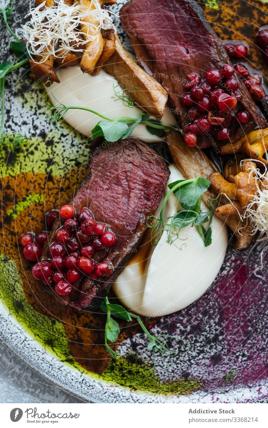 Rare steak with cranberry sauce rare sweet cheese mushroom herb meat plate beef food meal sliced piece exquisite served red gourmet juicy cooked prepared recipe