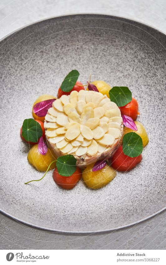 Fish tartare with almonds and cherry tomatoes fish restaurant served plate portion exquisite herb dinner raw cuisine appetizer food dish meal garnish snack