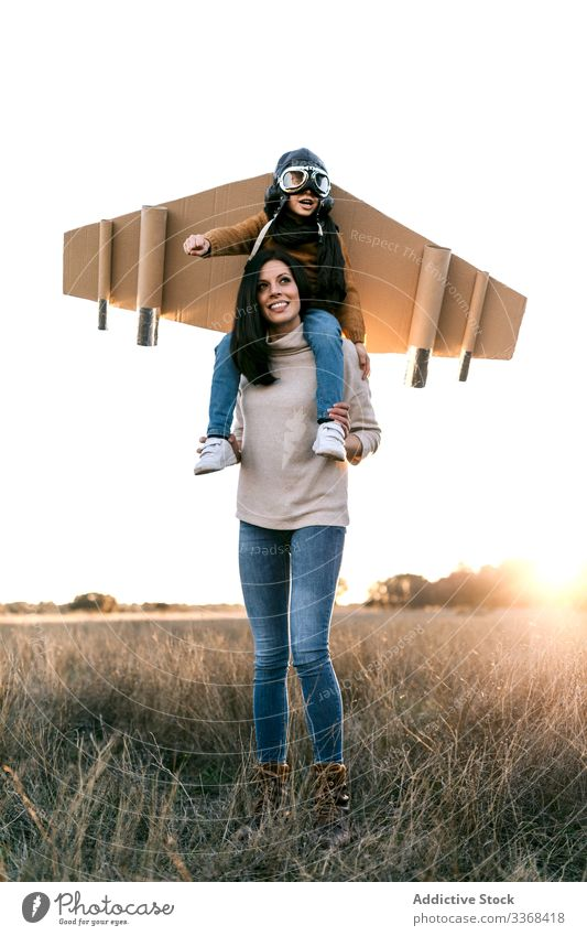 Cheerful mom and son playing together in field woman aviator dream game fly boy wear goggles wing mother imitate meadow cardboard on shoulders child parent kid