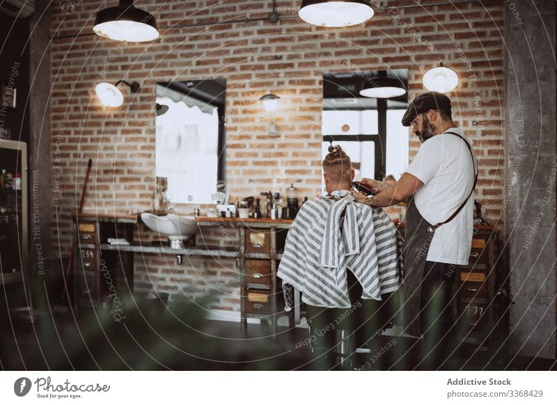 Hairdresser cutting a anonymous redhead man hair client trendy hairdresser barbershop bearded masculinity customer care salon hipster hairstylist handsome
