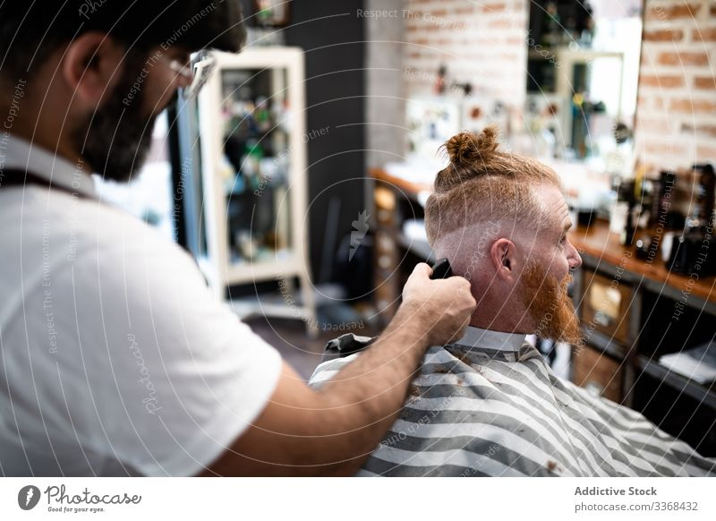 Hairdresser cutting a redhead man hair client trendy hairdresser barbershop bearded masculinity customer care salon hipster hairstylist handsome stylish