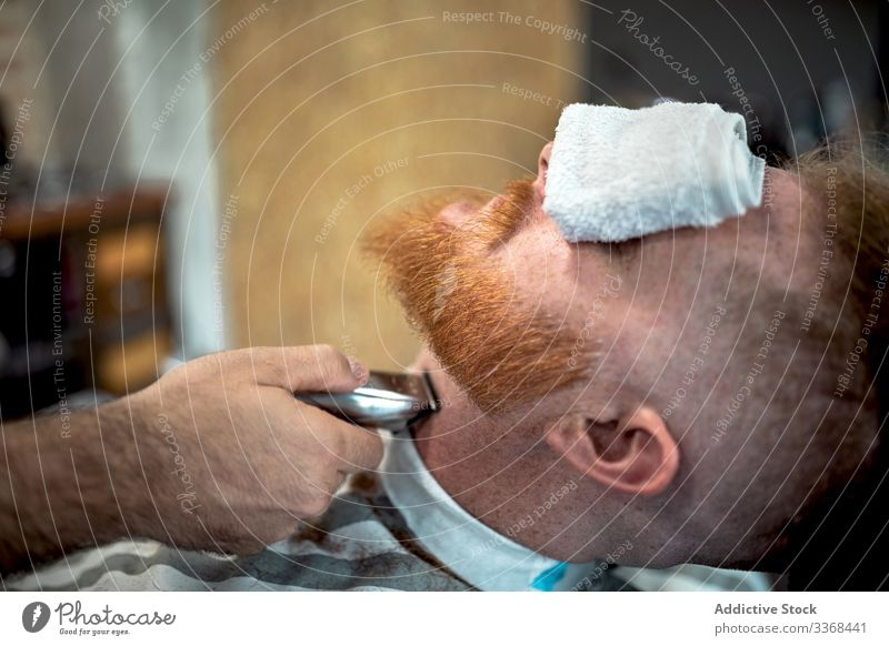Barber trimming redhead man beard men client trendy hairdresser barbershop masculinity customer care salon hairstylist handsome stylish relaxing stress relief