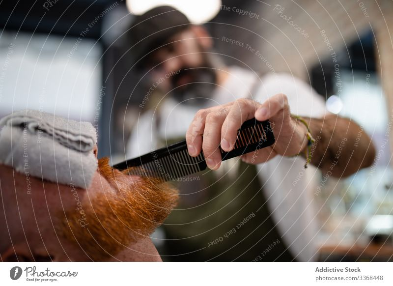 Anonymous barber trimming redhead man beard men client trendy hairdresser barbershop masculinity customer care salon hairstylist handsome stylish relaxing