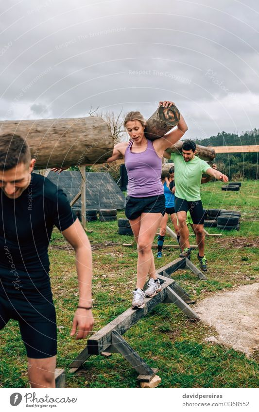 Group carrying trunks Contentment Sports Human being Woman Adults Man Smiling Carrying Authentic Strong Power Effort Competition balance exercise Tree trunk