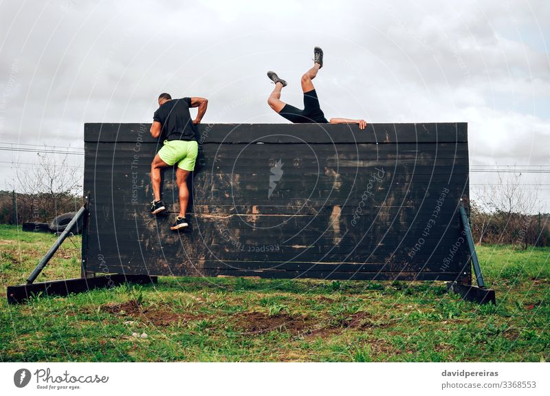 Runners in an obstacle course climbing wall Lifestyle Sports Climbing Mountaineering Human being Man Adults Group Jump Authentic Strong Black Effort Competition