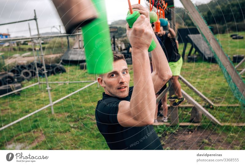 Participant obstacle course doing suspension Sports Human being Woman Adults Man Arm Group Observe Fitness Hang Authentic Strong Power Effort Competition