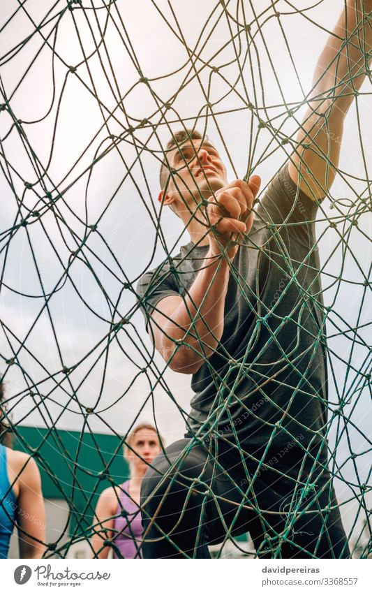 Male in obstacle course climbing net Lifestyle Sports Climbing Mountaineering Human being Man Adults Observe Authentic Strong Effort Competition view from below