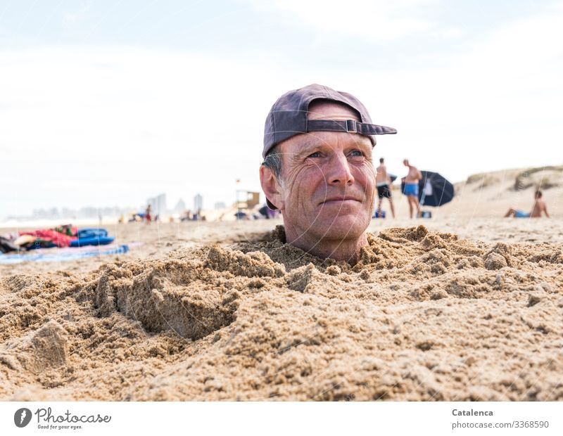 "Man with cap sticks head out of sand on beach Colour photo Exterior shot portrait Cap,"" Blue white background Sky Beach Summer Ocean vacation people bury"