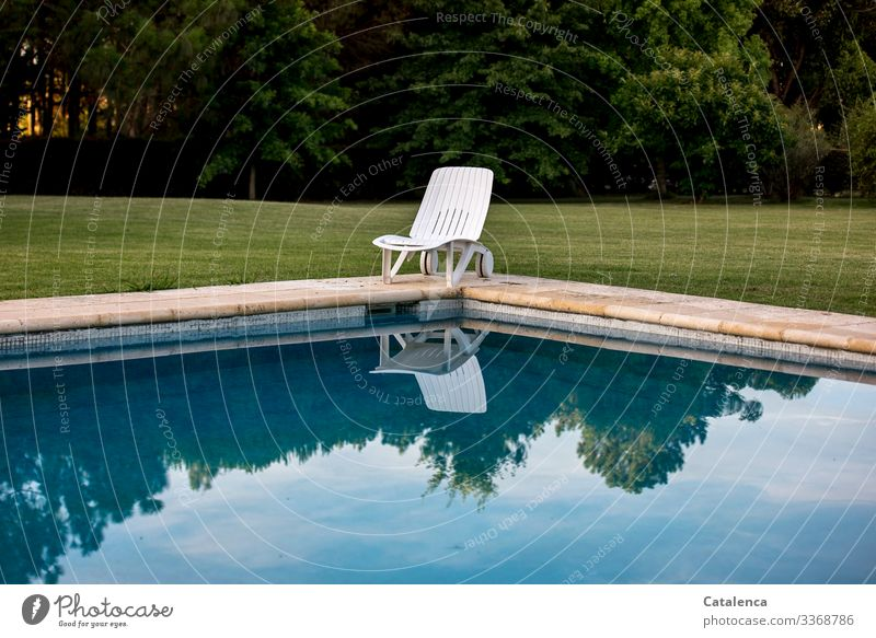 Corona thoughts | Stay at home - lonely deckchair stands at the edge of the pool, the sky is reflected in the water, a well-tended lawn and a row of trees can be seen in the background, the sun is setting.