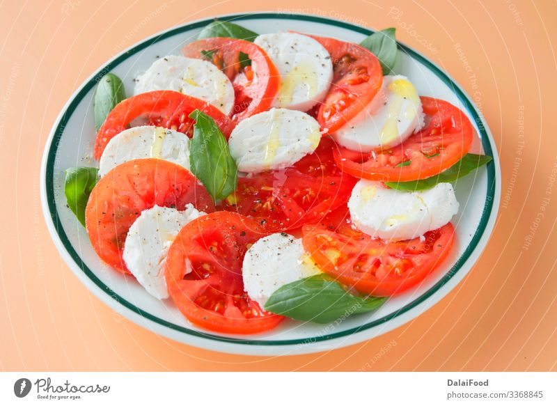 Caprese salad in brown background Cheese Vegetable Herbs and spices Nutrition Eating Diet Plate Table Fresh Red White Tradition Basil caprese salad Cooking food