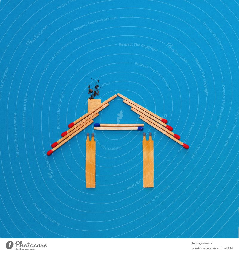 fire insurance, shape of the house made of matches. abstract house made with matches on blue paper background. Concept of home protection insurance with the importance of smoke detectors