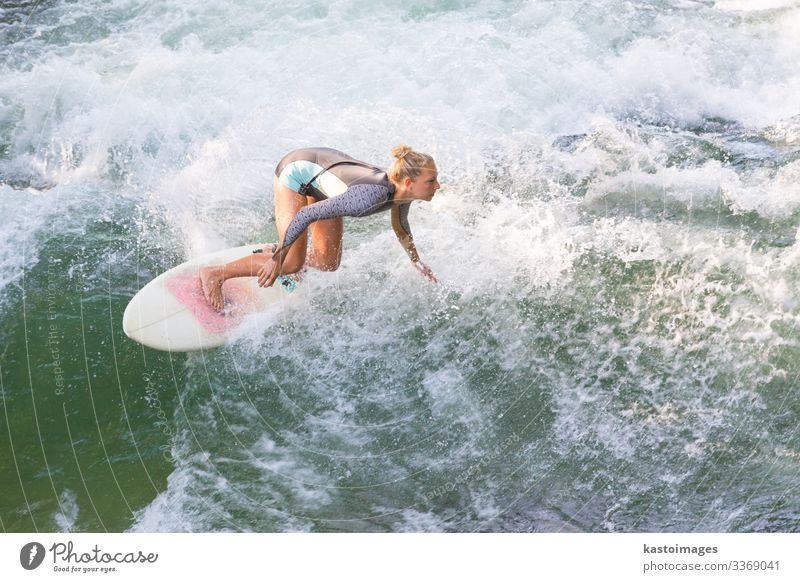 Sporty girl surfing on artificial river wave in Munich, Germany. Lifestyle Joy Beautiful Relaxation Vacation & Travel Summer Beach Ocean Sports Woman Adults