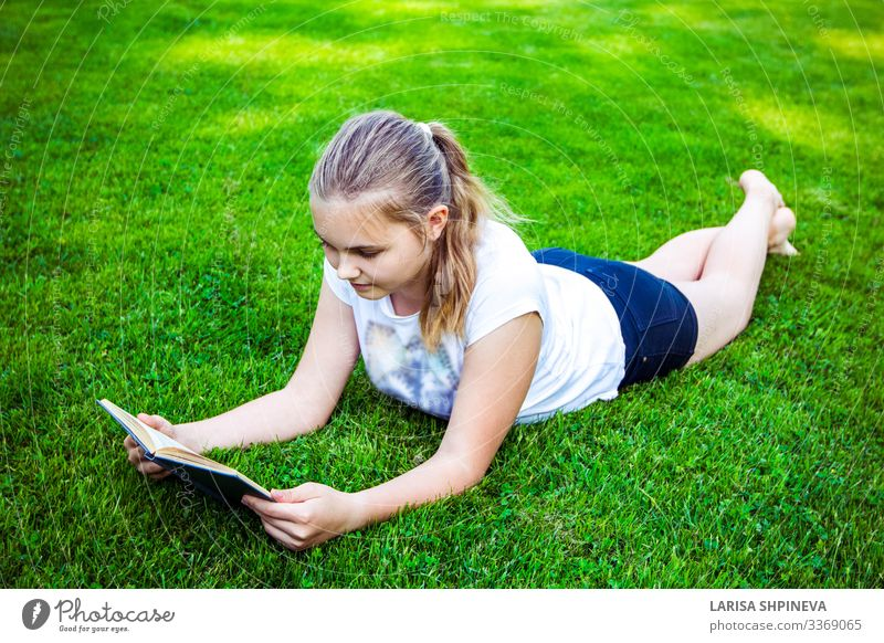 teenage girl lies on green grass and reads book in park Lifestyle Happy Beautiful Face Leisure and hobbies Reading Summer Garden School Study Human being Woman