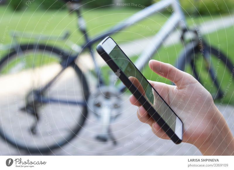 Smartphone in hand woman and blurred bicycle Lifestyle Vacation & Travel Sports Telephone PDA Screen Technology Internet Human being Woman Adults Hand Fingers