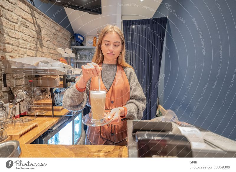 long lath Breakfast To have a coffee Beverage Hot drink Coffee Latte macchiato Glass Spoon Work and employment barista Workplace Café Human being Feminine