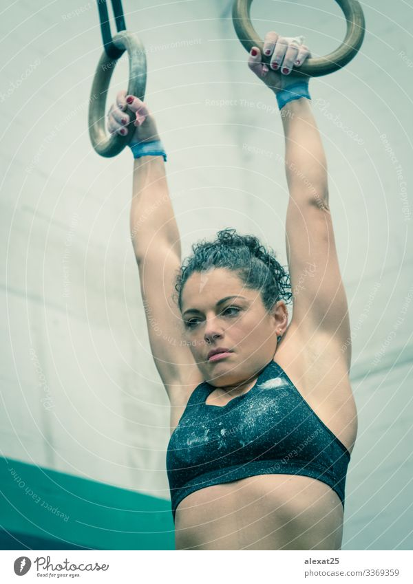Woman athlete hangs of the rings in the gymnastic Lifestyle Body Wellness Sports Human being Adults Hand Fitness Muscular Strong Determination Effort abs Action