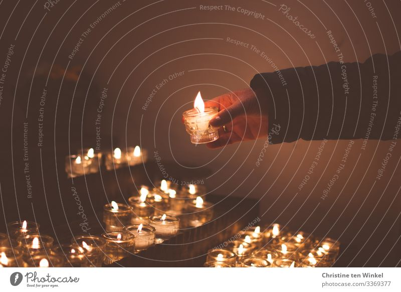 Woman lighting a candle on a candle altar Adults by hand 1 Human being 30 - 45 years 45 - 60 years Church Candlelight Candle flame Glass candle holder