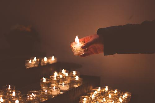 Woman lighting a candle on a candle altar Adults Hand 1 Human being 30 - 45 years 45 - 60 years Church Candlelight Candle flame Glass candle holder Candle altar