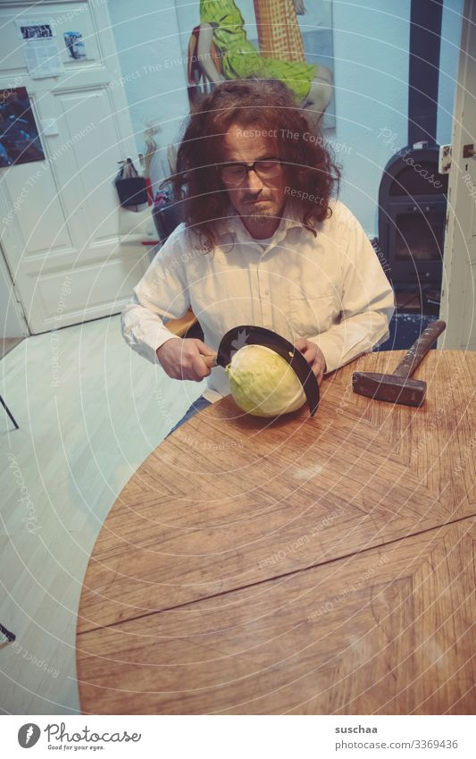 man sits at the kitchen table and tries to cut a cabbage with a sickle, with a hammer lying next to it, if this should prove too difficult ... Man cake Table