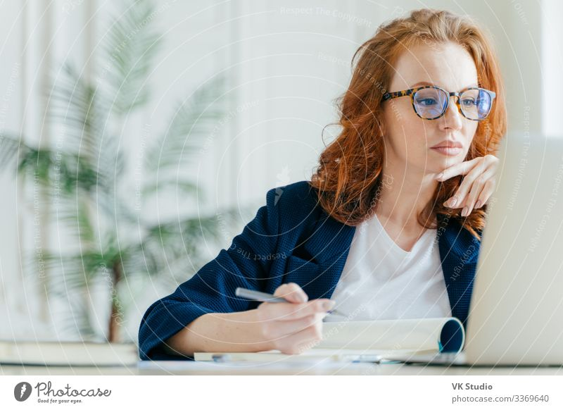 Serious experienced female coach makes records in notepad Work and employment Profession Workplace Office Business Company Computer Notebook Screen Technology