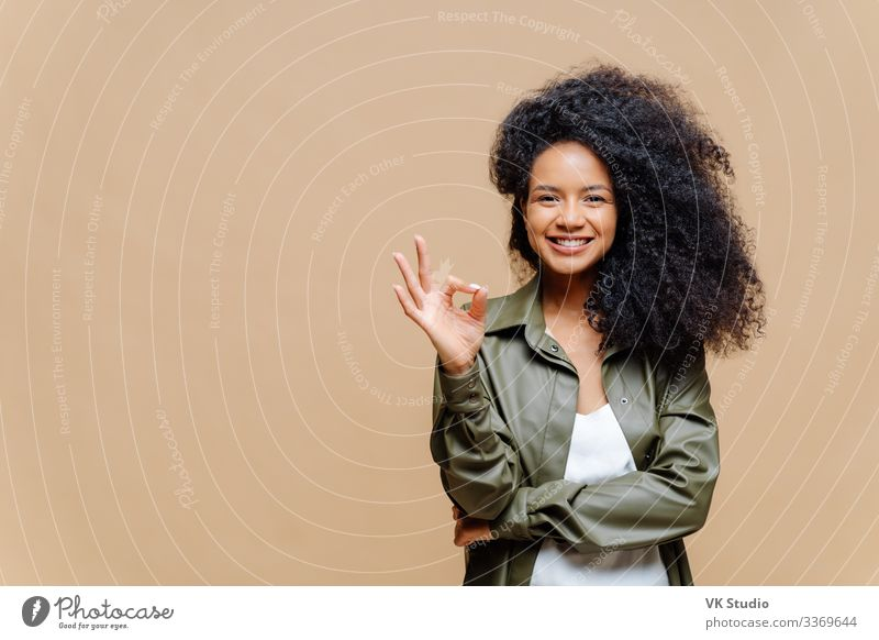 Indoor shot of pleasant looking curly woman has pleasant smile, makes okay gesture, excellent sign, gives approval, dressed in fashionable leather shirt, isolated over brown wall, blank space on left