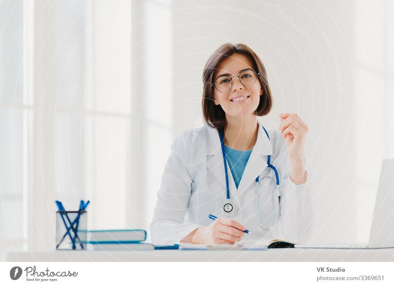 Young woman doctor writes on paper in clinic Happy Health care Medical treatment Medication Contentment Desk Table Work and employment Profession Doctor