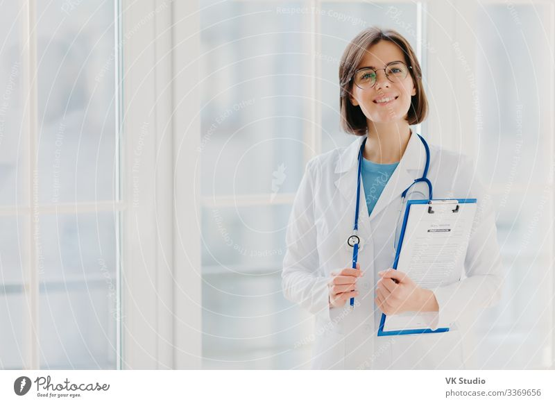 Beautiful intern holds clipboard with written papers and pen Happy Health care Medication Contentment Apprentice Work and employment Profession Doctor Hospital