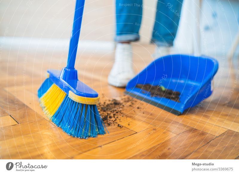 Latin man sweeping wooden floor with broom at home. housework household housekeeper object indoor equipment living concept apartment holding tidy tool closeup