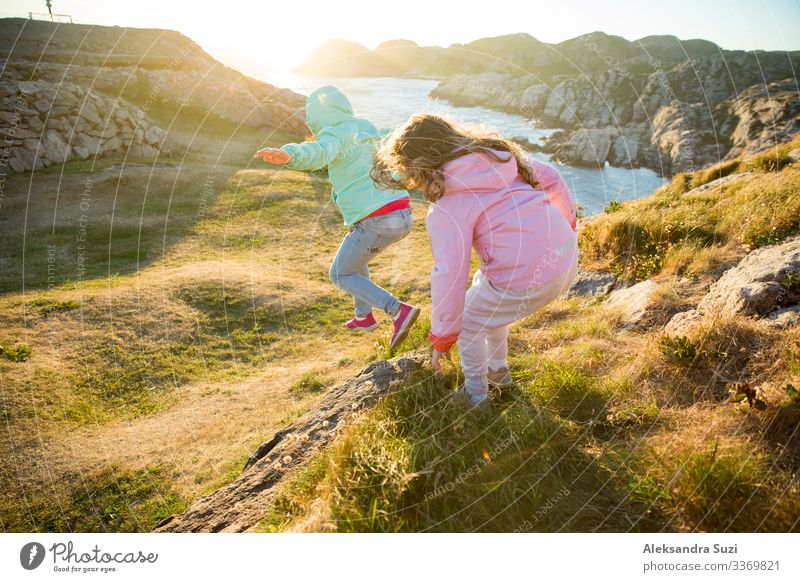 Two little girls play on rocky northern seashore. Run, laugh, jump, explore the coastal rocks and mountains. Travel and enjoy a great adventure in Norway.