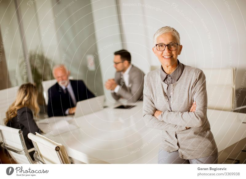 Cheerful senior businesswoman in office while other business people having meeting Lifestyle Office Business Meeting Human being Woman Adults Female senior