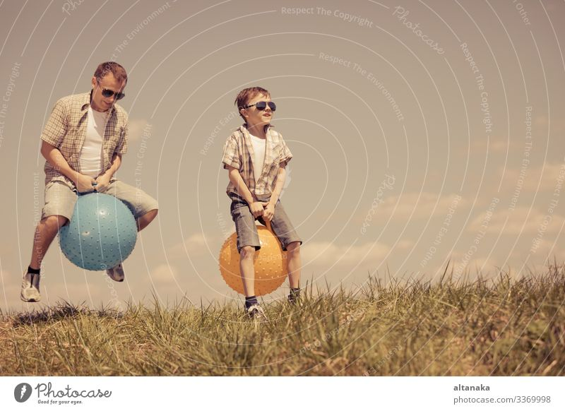 Father and son playing on the field at the day time. People having fun outdoors. They jumping on inflatable balls on the lawn. Concept of friendly family.