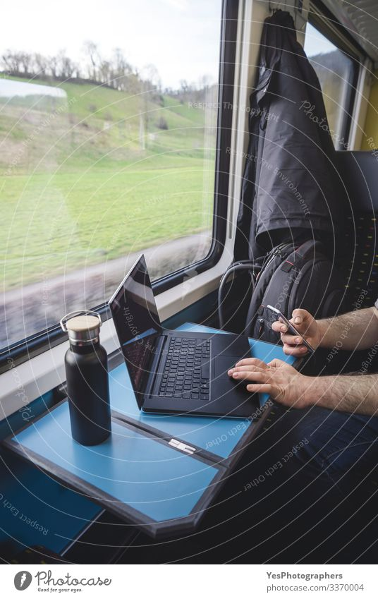 Man using laptop and phone inside train. Swiss train interior Vacation & Travel Tourism Trip Chair Table Work and employment Transport Passenger traffic