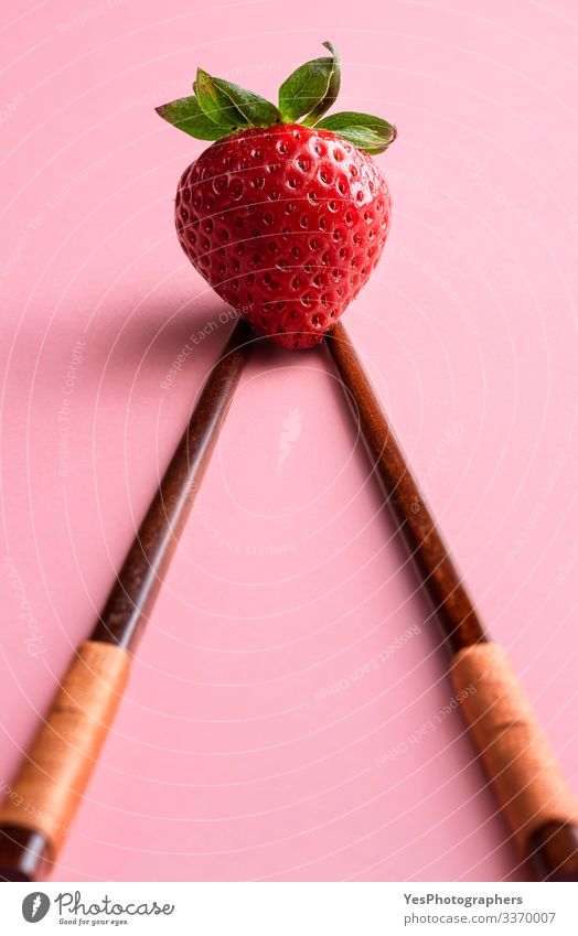 Ripe strawberry on bamboo chopsticks. Single strawberry Fruit Dessert Organic produce Vegetarian diet Fresh Natural Cute agriculture bamboo sticks Chopstick