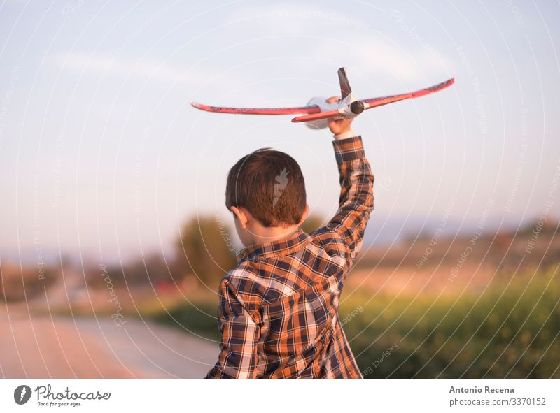 Little boy with toy airplane playing in outdoors image Playing Vacation & Travel Adventure Child Pilot Boy (child) Infancy Flower Meadow Street Airplane Toys