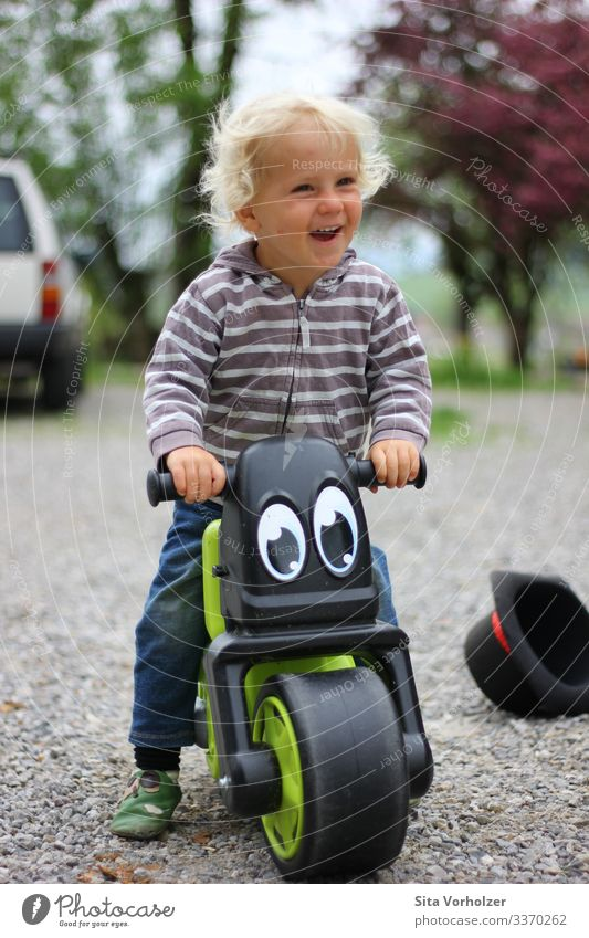Laughing boy on wheel Leisure and hobbies Summer Cycling Bicycle Parenting Child Human being Masculine Toddler Boy (child) Infancy 1 1 - 3 years Spring Park Hat