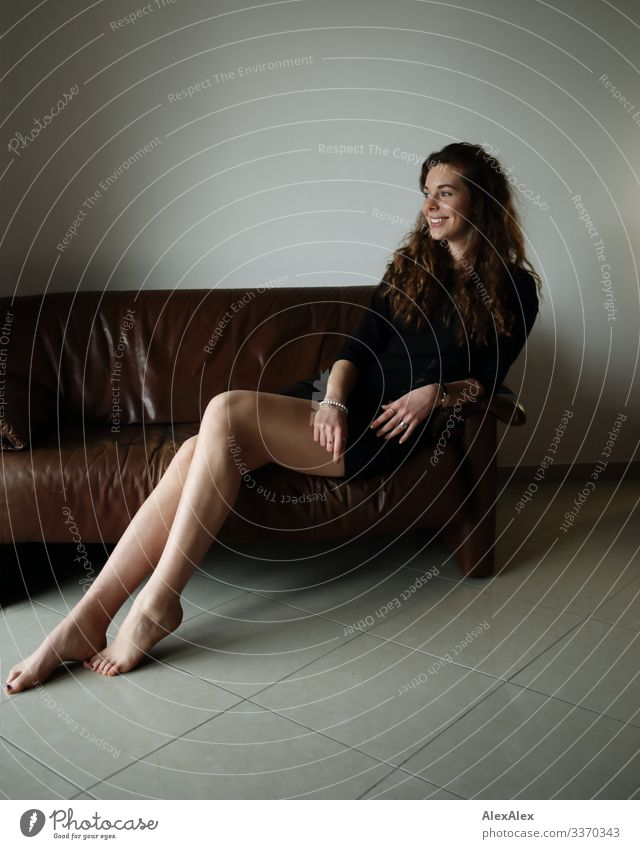 Portrait of a young woman on a couch Style Joy Beautiful Well-being Flat (apartment) Sofa Young woman Youth (Young adults) Legs 18 - 30 years Adults Dress