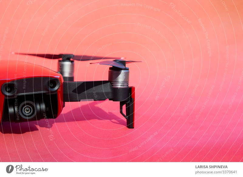 Drone quadcopter with camcorder on red background Leisure and hobbies Pilot Camera Technology Vehicle Airplane Helicopter Aircraft Robot Observe Movement Flying