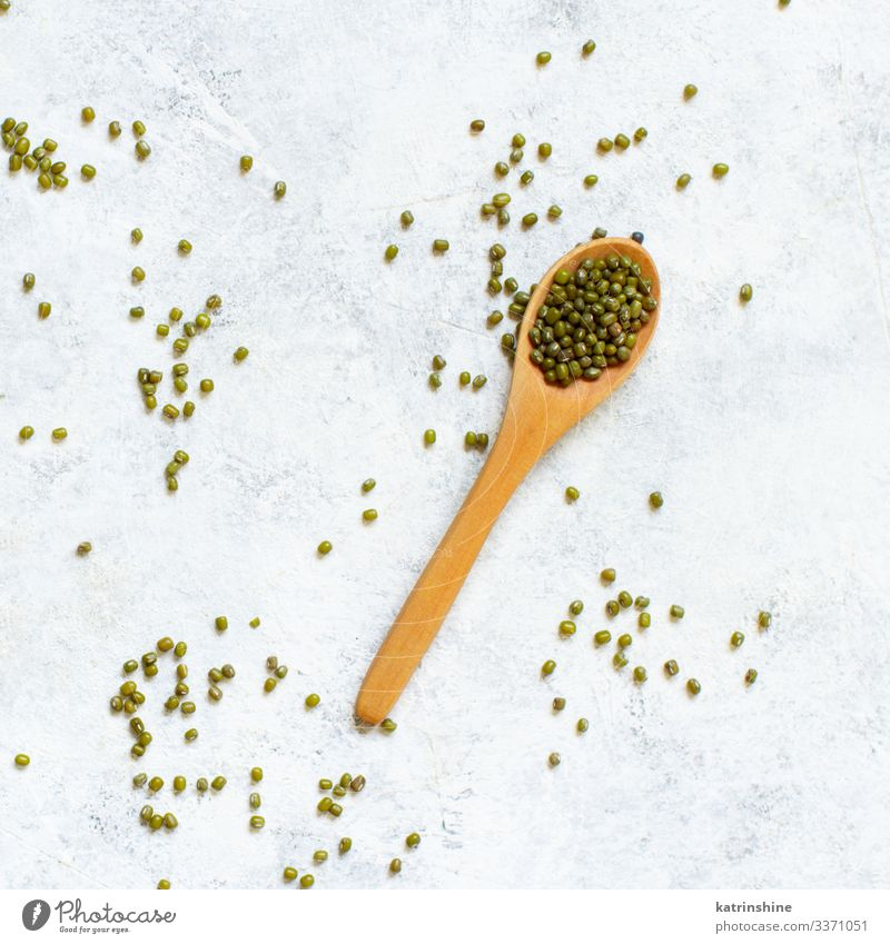 Dried mung beans with a spoon on a white background Vegetarian diet Diet Spoon Table Above Green White Beans fiber food health healthy Ingredients Kidney legume