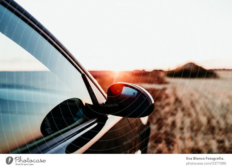 close up view of a car and rear mirror at sunset on a field. Travel concept travel sunny countryside yellow nobody sporty utility nature destination vehicle