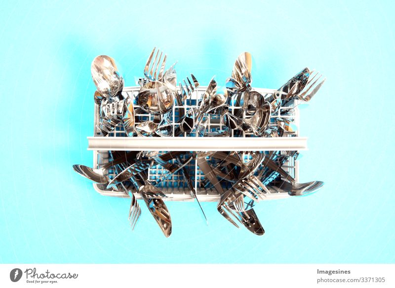 Cutlery in a dishwasher - cutlery basket. Top view. blue background with space for text. Spoons, forks and knives cleaned in a crockery basket, close-up