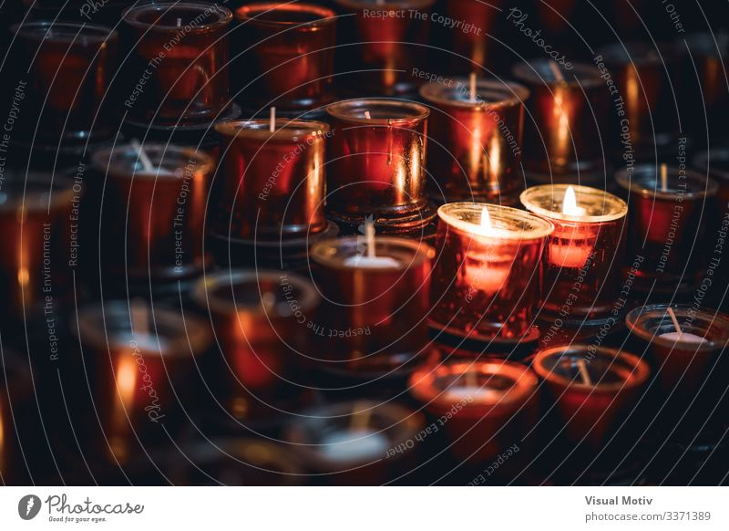 Two burning candles among several rows of red candles in a church Relaxation Meditation Warmth Church Candle Bright Hope Colour Peace Belief Religion and faith