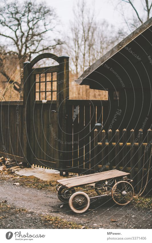wooden cart in front of wooden hut Door Goal Wooden house Village Village idyll Trailer out Wooden fence Children's game children's toy
