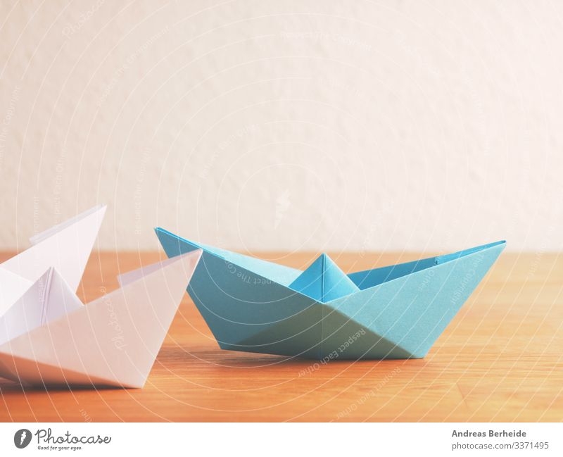 Teamwork business concept with paper boat on a wooden table background blue color compass competition copy space creative creativity difference different