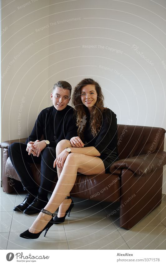 Young man and young woman sitting together on a brown leather couch and smiling Lifestyle Style Joy already Harmonious Flat (apartment) Sofa Young woman