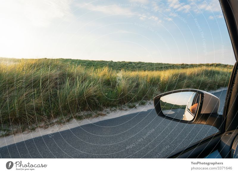 Car window view with grassy dunes and road on Sylt island Vacation & Travel Tourism Trip Summer Mirror Landscape Grass Street Driving Perspective Germany