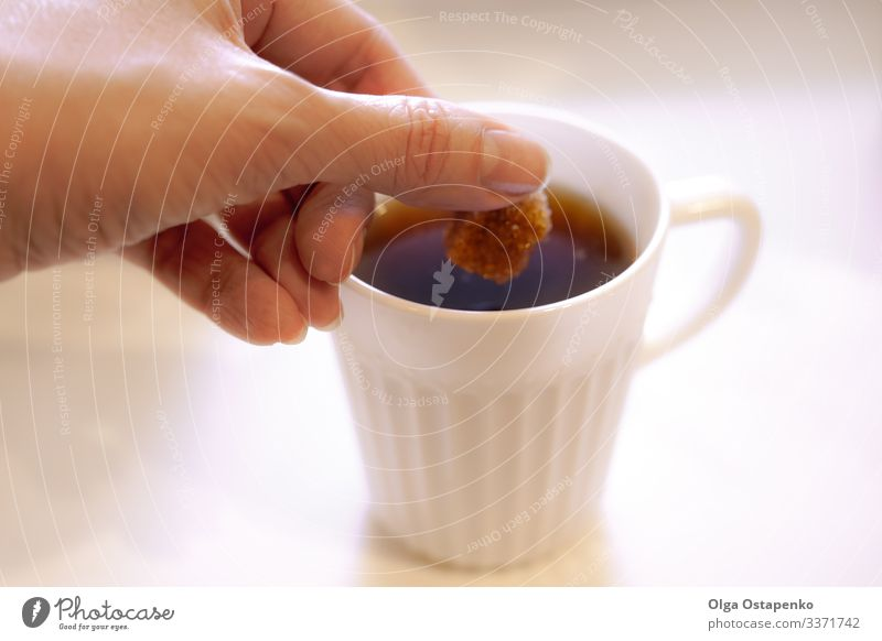 In a white cup the woman's hand puts a piece of brown sugar Table Hand Brown White Candy Sugar Close-up Woman Hot Beverage Cup Coffee Café Breakfast Natural